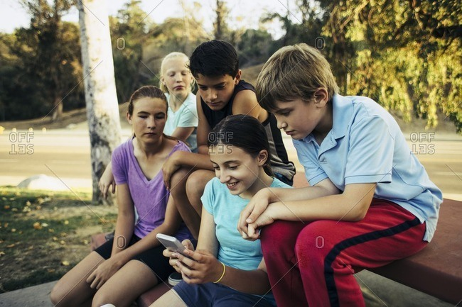 Friends looking at girl using mobile phone in park