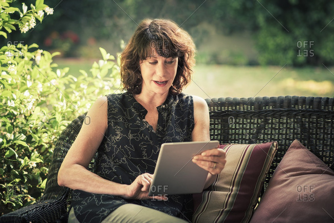 Mature woman using digital tablet while relaxing in backyard
