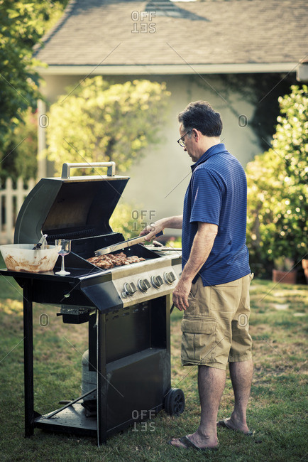 Full length of mature man grilling meat on barbecue in backyard