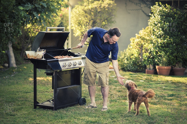 Full length of mature man feeding grilled meat to dog in yard