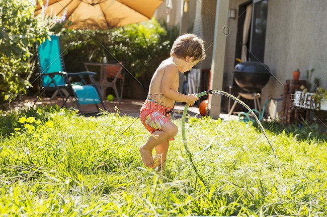 Side view of boy watering grass at backyard on sunny day