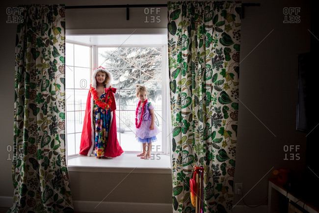 Two young girls playing dress up in window