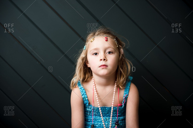 Portrait of young girl playing dress-up with jewelry