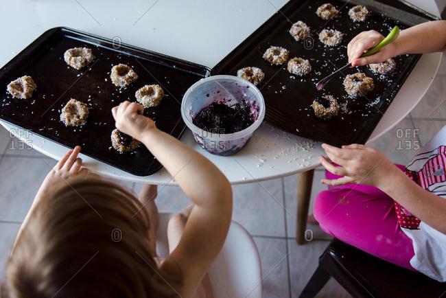 Children making jam thumbprint cookies