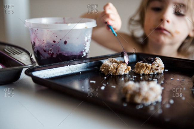 Girl filling cookies with jam