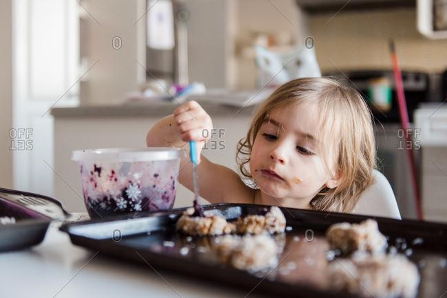 Young girl putting jam in thumbprint cookies