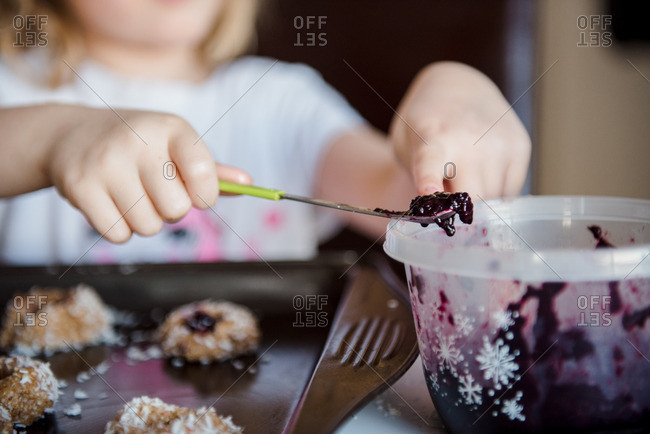 Child scooping jam from bowl for cookies