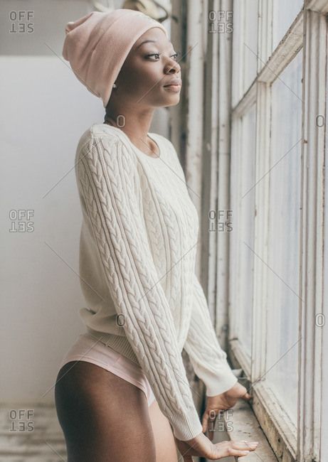 Woman in cable knit sweater standing at window