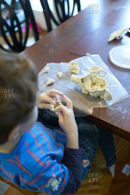Boy at table playing with clay