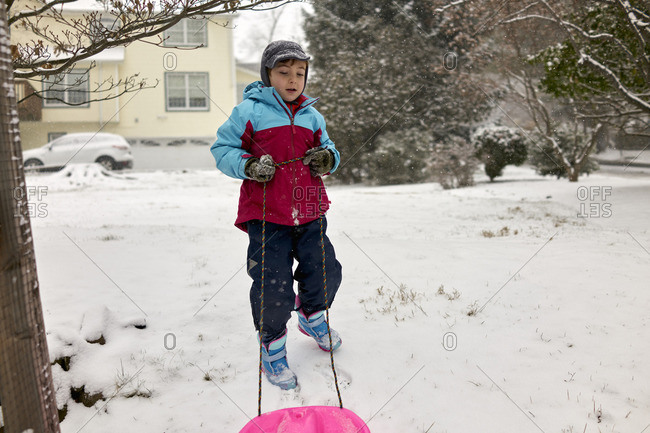 Boy pulling a sled in yard