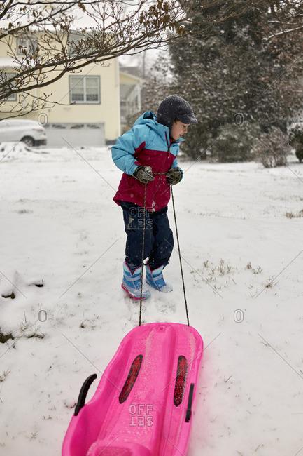 Boy pulling a sled in snowy yard