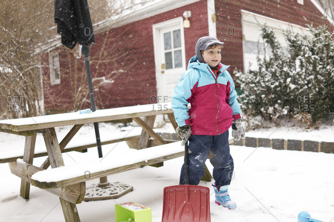 Boy with snow shovel on patio