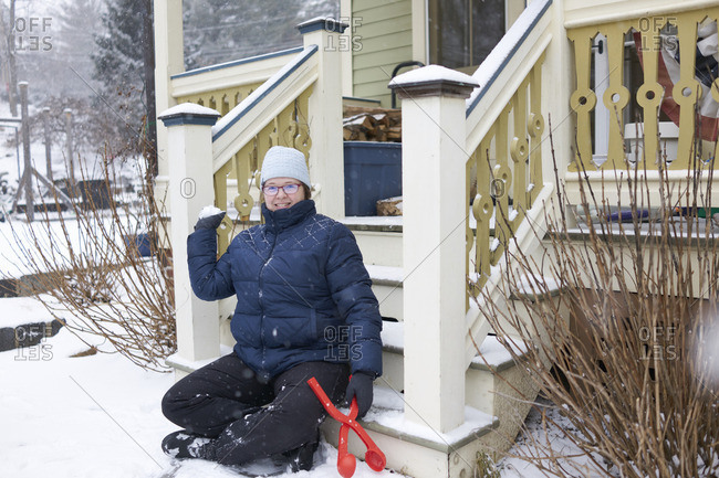 Woman sitting on porch with snowball maker