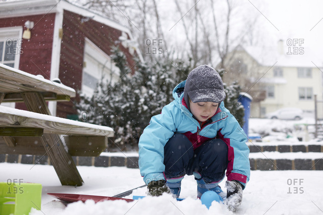 Young boy playing in snow in backyard