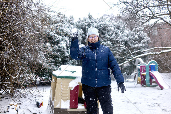 Woman playfully throws a snowball in backyard