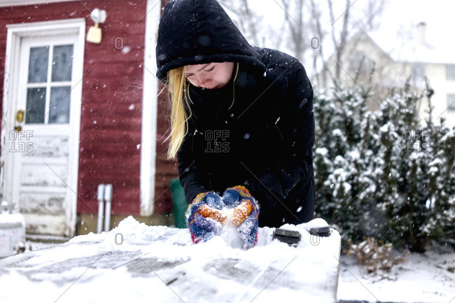 Woman sculpting a snowball on picnic table