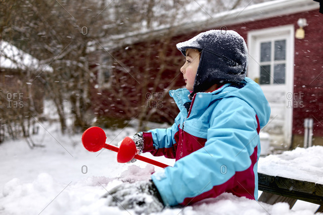 Boy playing with snowball maker in backyard