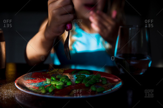 Child eating edamame at table