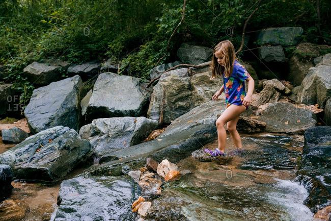 Girl exploring rocky stream