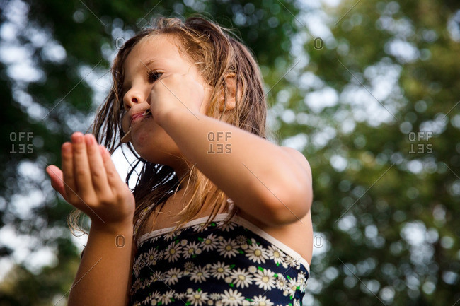 Young girl in bathing suit eating an ice cream bar