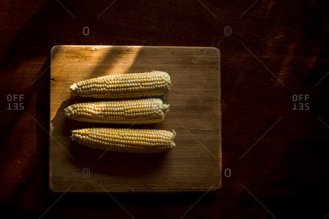 Fresh husked ears of corn on wooden cutting board