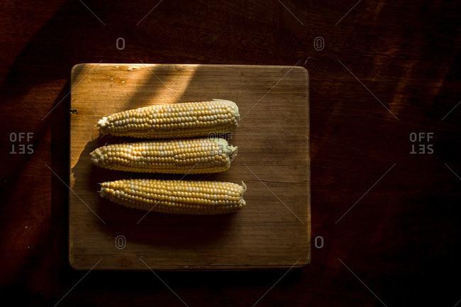 Fresh husked ears of corn on wooden cutting board