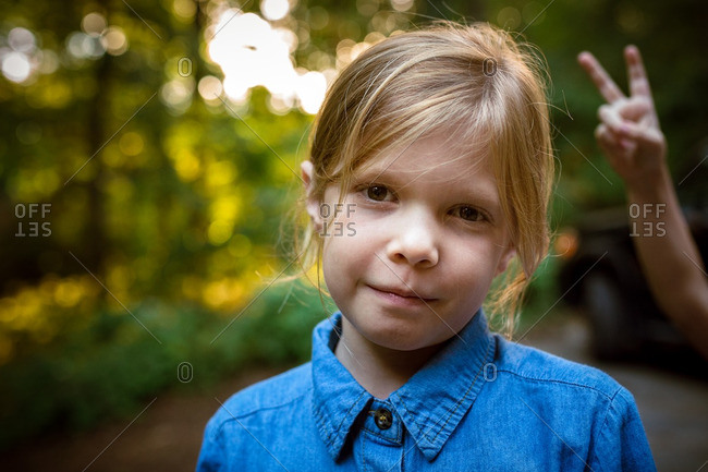 Portrait of a cute girl with child's hand in background
