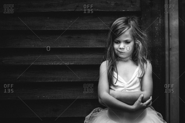 Portrait of a young girl in tutu standing against barn with quizzical expression