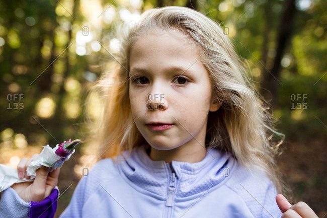 Blond girl eating ice pop in forest