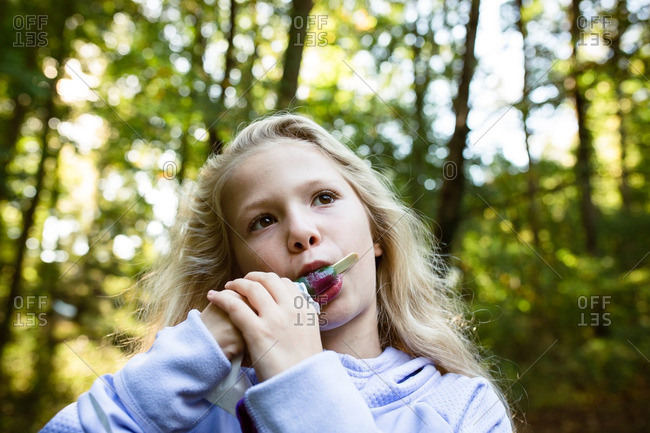 Young girl enjoying an ice pop in the woods