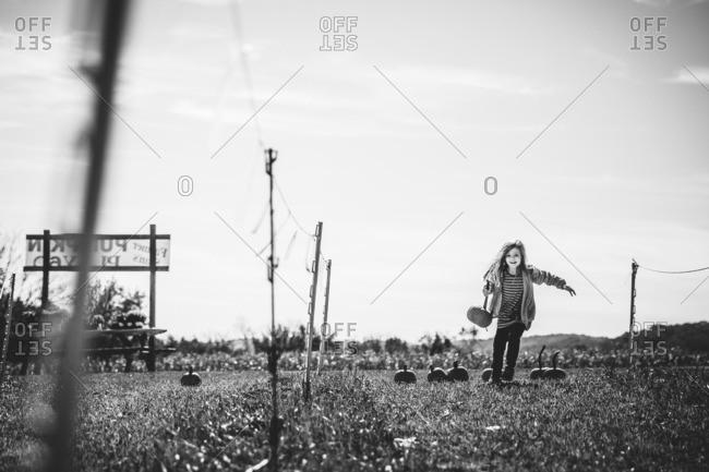 Girl running in field with pumpkin