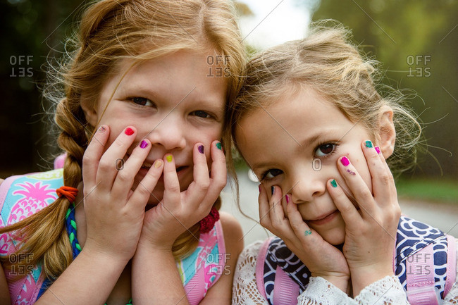 Two young girls with multicolored fingernails