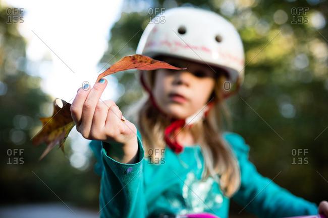 Girl in bike helmet holding autumn leaf