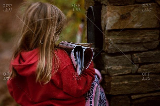 Girl taking mail out of mailbox