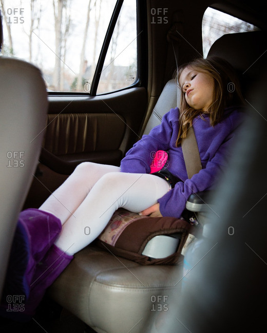 Young girl asleep in her booster seat