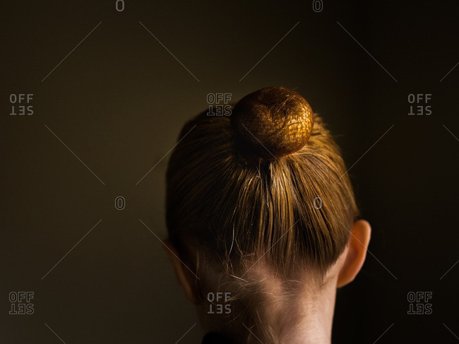 Back view of young girl with red hair in a bun