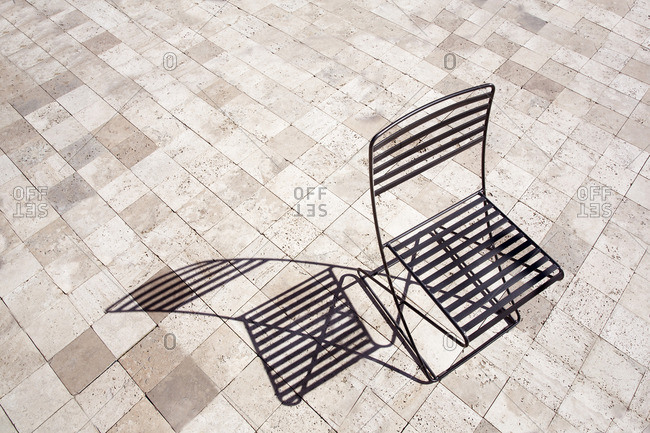 Empty patio chair and shadow