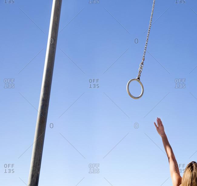 Person reaching up for gymnastic ring at outdoor exercise facility