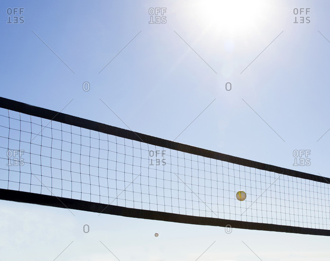 Volleyball net and ball in flight