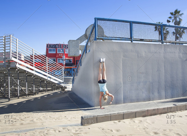 Los Angeles, California - February 1, 2016: Woman doing a handstand with one hand at Muscle Beach in Venice