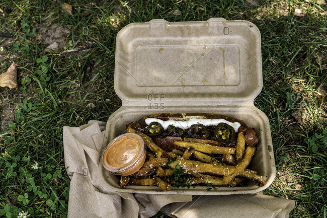 Takeout box with hot dog, fries and jalapenos