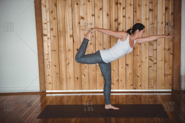 Woman practising yoga in fitness studio