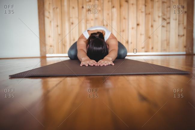 Woman performing yoga in fitness studio