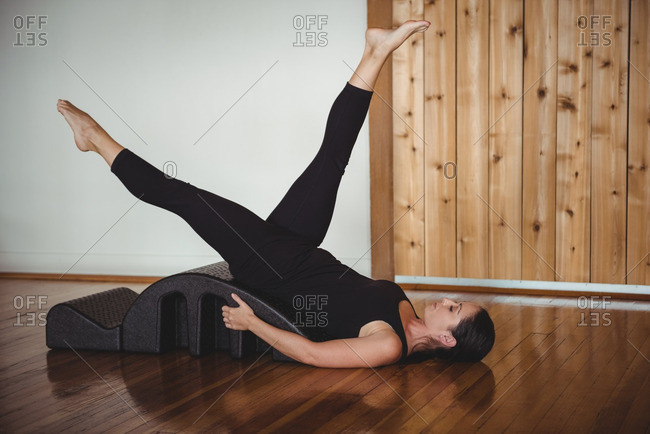 Woman exercising with yoga back arch in fitness studio