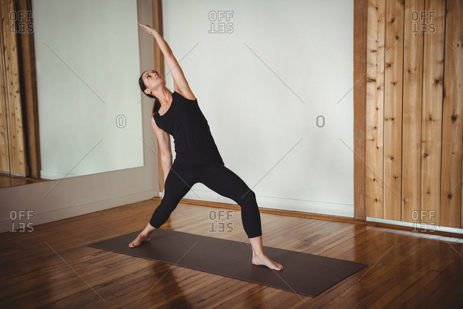 Woman performing yoga in fitness studio