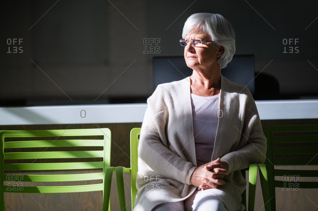Thoughtful senior woman sitting on chair in hospital