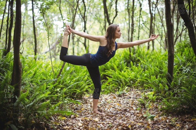 Woman performing standing bow pose yoga in forest on a sunny day