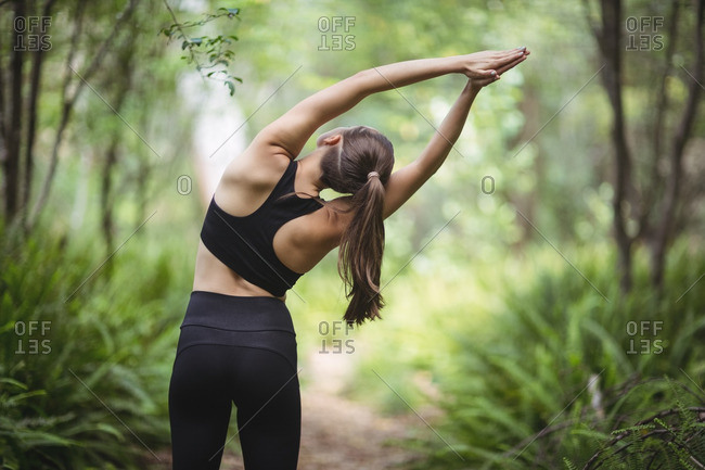 Rear view of woman performing stretching exercise in forest