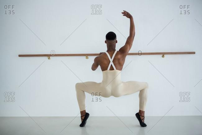 Rear view of ballerino practicing ballet dance in the studio