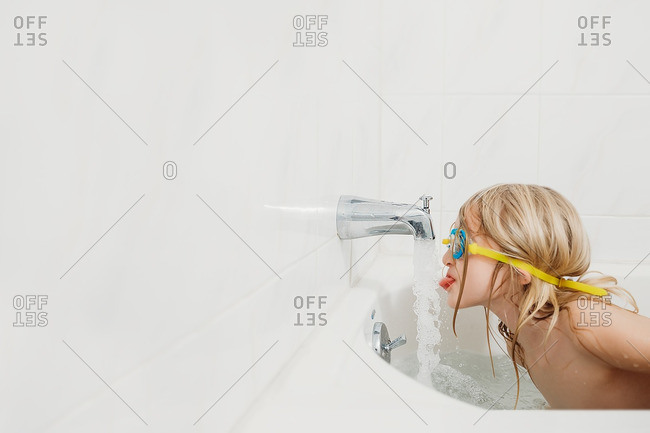 Little girl drinking from faucet while wearing goggles in the bathtub
